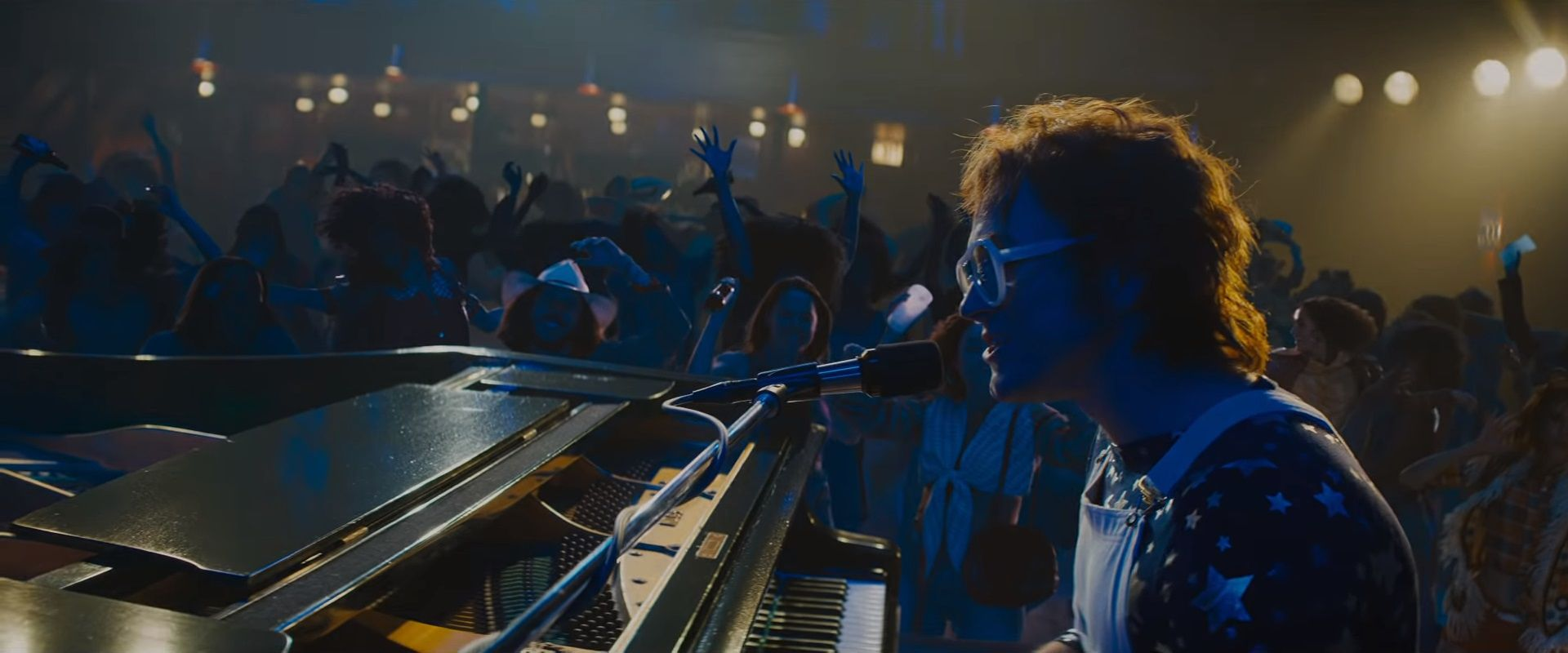 Rocketman (2019) scene singing an playing piano at concert